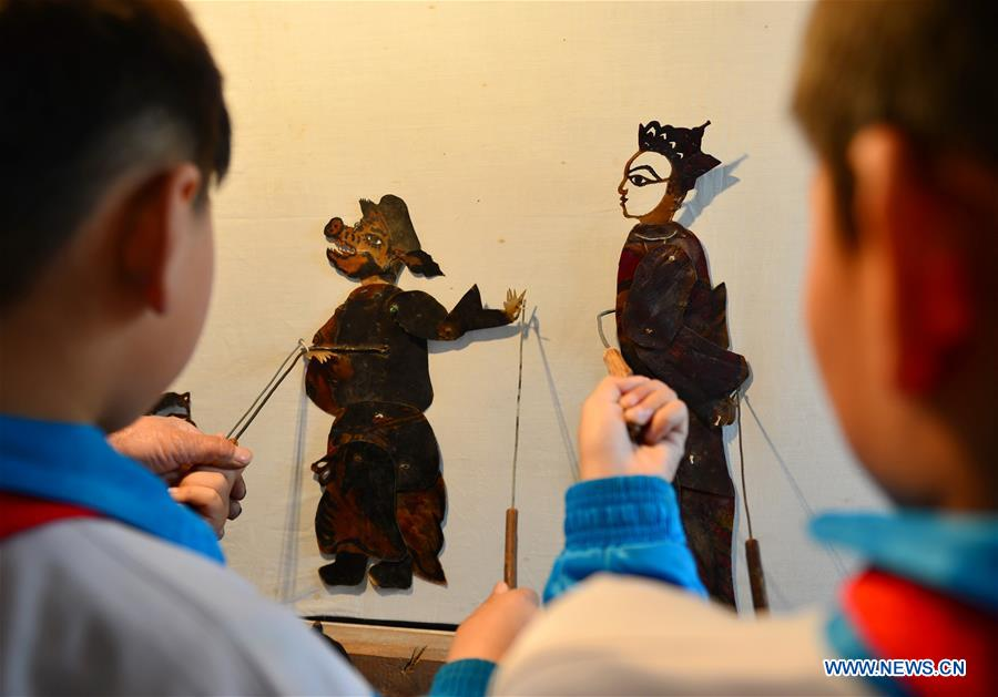 Shadow puppet artists teach students traditional culture